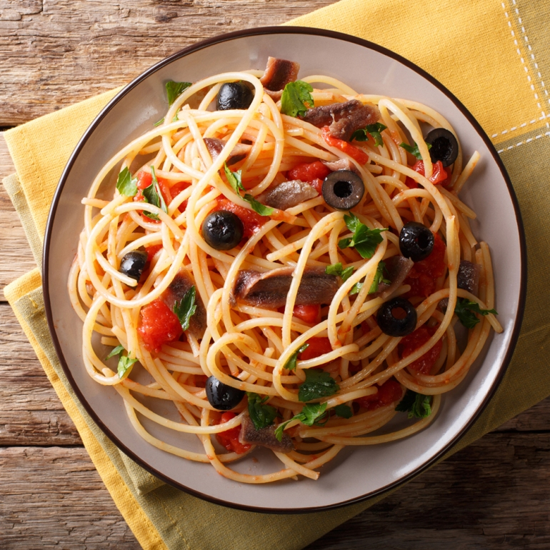 Traditional pasta alla puttanesca with anchovies, tomatoes, garl