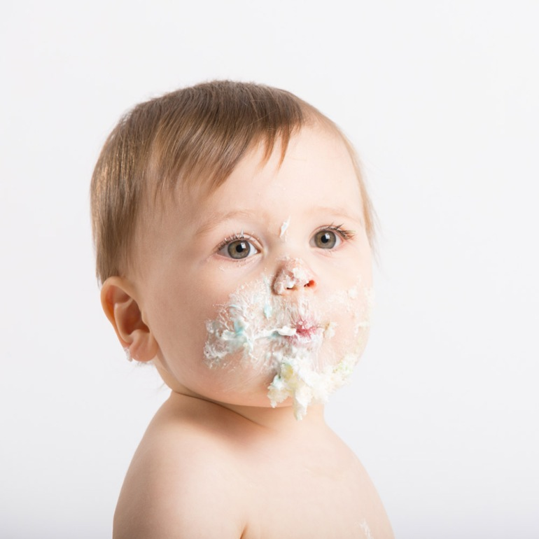 Close Up of Baby with Face Full of Cake and Frosting